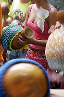 Young women play calabash or bottle gourd used as percussion instrument in street carnival, bloco de rua, Santa Teresa district.