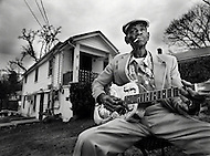 African-american blues musician, John Dee Holeman, sits on a chair outside of his Durham, NC home and smokes a cigarette while playing his guitar.