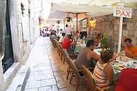 View along the Prijeko street with restaurants with outside seating long tables and chairs lining the street under sun shades. The Konoba Pax restaurant with some tourists having dinner Dubrovnik, old city. Dalmatian Coast, Croatia, Europe.
