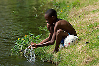 A kid washes his face and hands in water after playing football