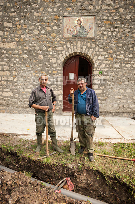 Ditch diggers putting in a drainage pipe at Sveto Vaznesenje Serbian Orthodox Church built of stone in the late 17th century.<br /> <br /> Mokra Gora is one village but three mountains, one village but two churches-one in Krsanj, another in the centre of Mokra Gora.The first had been burnt down three times by the Turke and people of Mokra Gora persistently erected it from the ashes.According to oral tradition the church of Sveto Vaznesenje had been built at the end of 17th century, before the great migration of the Serbs, on a very hidden spot near the river Beli Rzav, surrounded by very high rocks on both sides. After the three burnings of the church in Krsanj, people of this village built a stone church that still esist and there is a valuable iconostasis from<br /> the year 1849 with the icons painted in the same year. It's the icon of Jesus Christ, the big archpriest on the throne and the icon of Mother of God with Christ on the throne. People of Mokra Gora had been trying to build a church in Mokra Gora since 1876.<br /> It is reported that the icone of Holly Mother of God had been brought from Krsanje to Mokra Gora three times, but all over again it returned by itself to Krsanje to the site of a fire, and not until 1945 Mokrogorci built the church and erected the paris home.