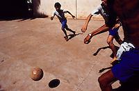 Barefoot boys play soccer in the street, Rio de Janeiro, Brazil.