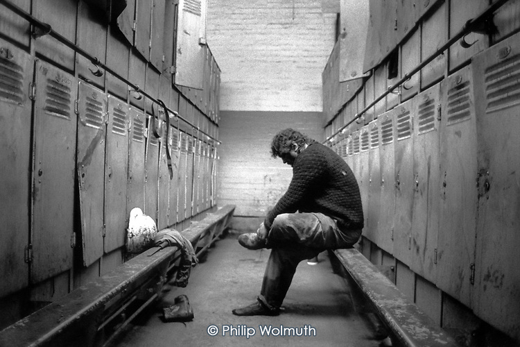 A miner takes off his boots at the end of a shift at Taff Merthyr colliery, South Wales. The South Wales valleys used to employ 250,000 miners in 400 pits.