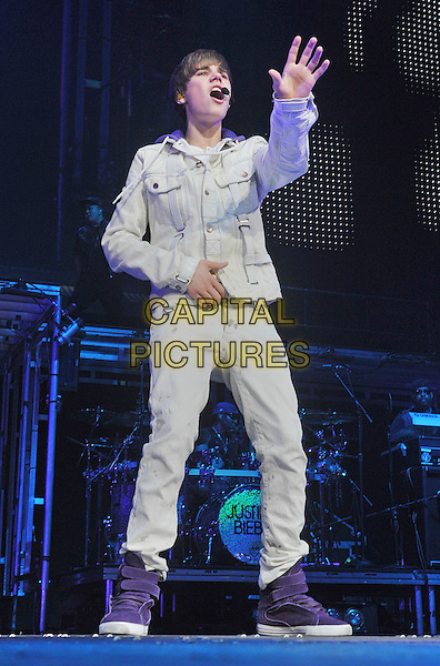 """JUSTIN BIEBER.Justin Bieber performs to a sold outcrowd at a stop on his """"""""My World Tour 2010"""" held at the Consol Energy Center, Pittsburgh, PA, USA..December 13th, 2010.stage concert live gig performance music full length white jean denim jacket purple trainers sneakers hi high top singing hand arm.CAP/ADM/JN.©Jason L Nelson/AdMedia/Capital Pictures."""