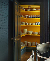 Glassware and dinner service are stored in a conveniently created walk-in corner cupboard in the dining room the interior of which has been painted in yellow gloss