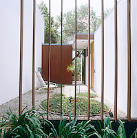 A wooden partition and garden door screens the entrance of the house and garden beyond