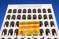 """Attivisti di Greenpeace espongono uno striscione di 300 metri quadri contro il nucleare, sulla facciata del Palazzo della Civilta' e del Lavoro (Colosseo Quadrato) all'Eur, Roma, 19 gennaio 2010, a pochi passi dalla sede di Confindustria, durante il seminario Enel sul progetto nucleare in Italia..Greenpeace climbers activists unroll a 300 mq banner reading """"Stop Nuclear Madness"""" on the facade of the Palace of Civilizatin and Labour (Square Colosseum) at the EUR quarter, close to the Confindustria entrepreneurs association headquarters, in Rome, 19 january 2010, during an Enel's meeting on the nuclear restoration project in Italy..UPDATE IMAGES PRESS/Riccardo De Luca"""