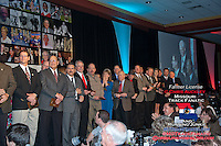 Current and past members of the Jefferson City High School Track and Field family stand on the stage with recognition plaques while long-time coach Dennis Licklider (top on projector screen)  gives an acceptance speech on behalf of the program as it is inducted into the Missouri Sports Hall of Fame, Sunday, January 27, 2013 in Springfield, MO.