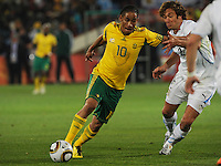 South African midfielder Steven Pienaar builds up a head of steam on the dribble towards Uruguay's goal, as defender Diego Lugano looks to slow his progress. Uruguay defeated South Africa, 2-0, in both teams' second match of play in Group A of the 2010 FIFA World Cup. The match was played at Loftus Versfeld in Pretoria, South Africa June 16th.