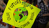 A demonstrator peers through her placard which says 'Our Future In Your Hands' during the Climate Change demonstration, London, 21st September 2014. © Sue Cunningham