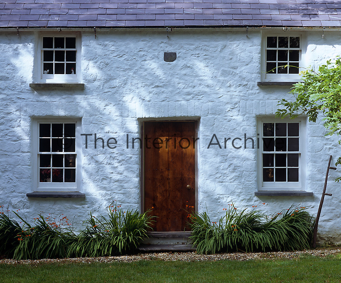 This traditional Welsh cottage has a whitewashed facade and a slate roof