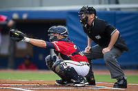 Danville Braves catcher Trey Keegan (23) reaches for a pitch as home plate umpire Russ Weich looks on during the game against the Pulaski Yankees at Legion Field on August 7, 2015 in Danville, Virginia.  The Yankees defeated the Braves 3-2. (Brian Westerholt/Four Seam Images)