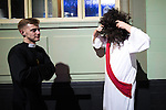 © Joel Goodman - 07973 332324 . 27/12/2016 . Wigan , UK . A man dressed as Jesus Christ puts on a large curly black wig as another man dressed as a clergyman walks by . Revellers in Wigan enjoy Boxing Day drinks and clubbing in Wigan Wallgate . In recent years a tradition has been established in which people go out wearing fancy-dress costumes on Boxing Day night . Photo credit : Joel Goodman