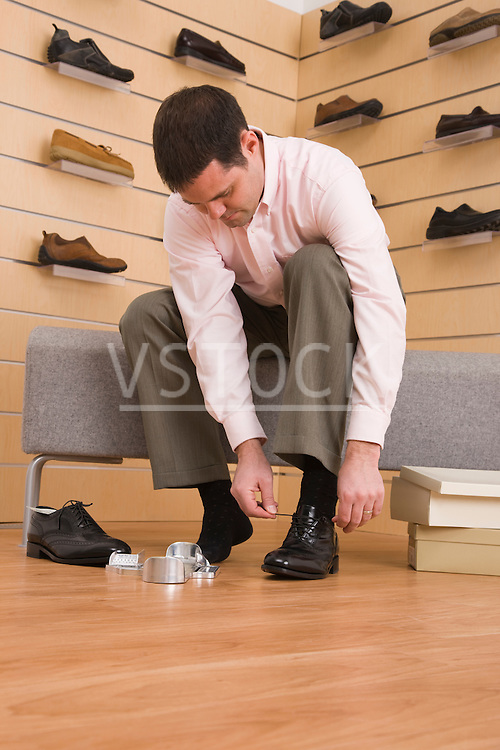 USA, Illinois, Metamora, Man trying on shoes in store