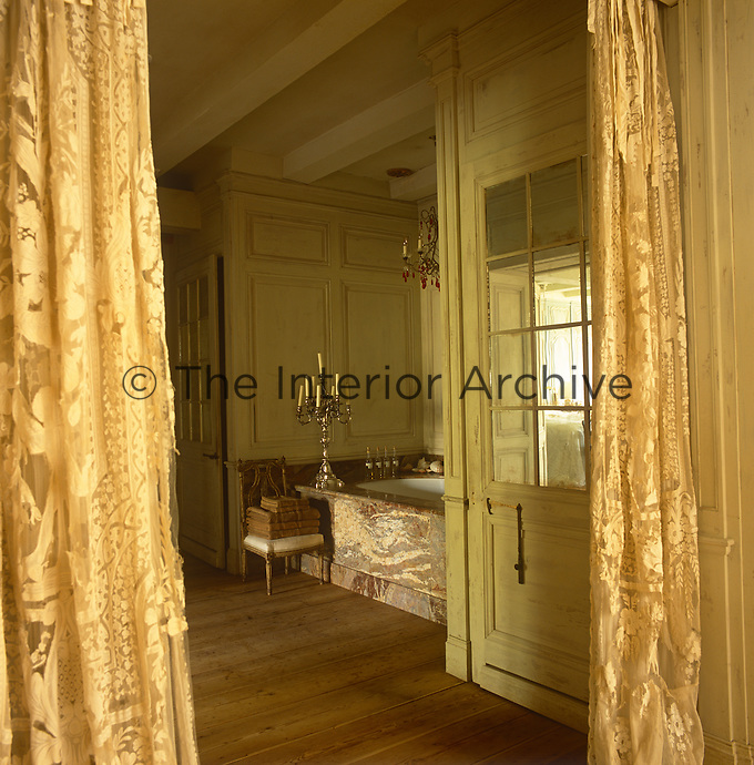 A view past a pair of gold curtains into a bathroom with yellow painted panelling and a wood floor. A bath with a marble surround is set in a recess.