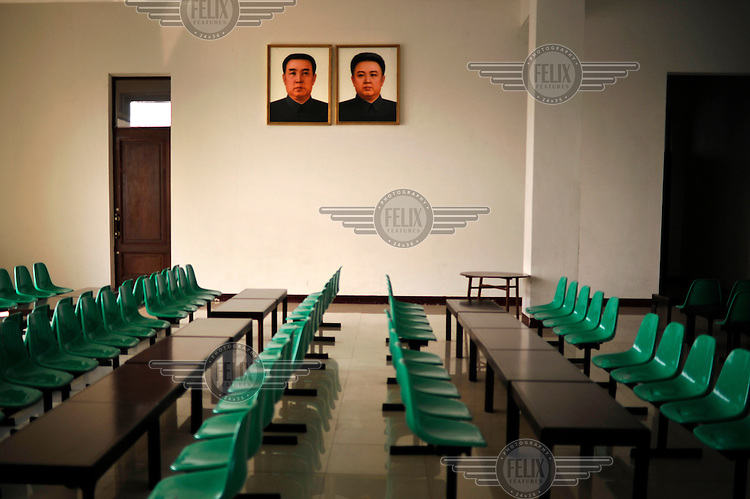 Portraits of Eternal President Kim Il-sung (left) and Supreme Leader Kim Jong-il (right) stare down from the otherwise bare wall of the waiting room of Sinuiju train station.
