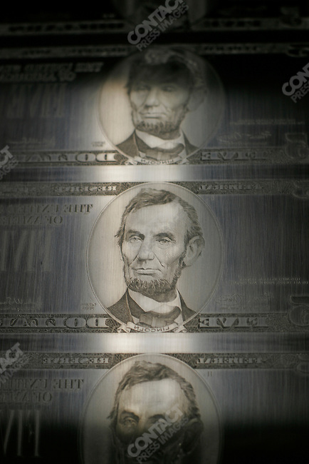 At the Bureau of Engraving plates for printing the $5 bill featuring Abraham Lincoln's face are inspected and cleaned by staff, Washington D.C., June 3, 2005