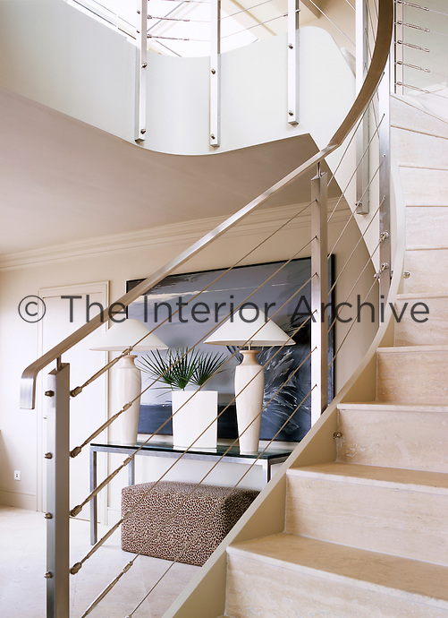 A modern hallway with an elegant curving staircase with a steel banister and wooden treads. Two lamps stand on a console table with an ottoman beneath.