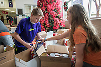 STAFF PHOTO ANTHONY REYES &bull; @NWATONYR<br /> Alex Bowers, 13, left, and Alexis Samarin, 13, both students at Tyson Middle School organize donated food Tuesday, Dec. 16, 2014 at the school in Springdale. A few students from Todd Holland's class organized the food to be delivered to local charities. The school collected non-perishable food items to be given to local agencies and families at the school in need.