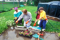 Learning to plant flowers, grandma and grandson intergenerational -gardening in the backyard, family time teaching young child by older adult person, mother and father and son