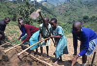 Young school girls preparing ground for planting
