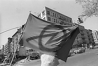 Man waving the punk anarchist flag on Avenue A in the East Village.