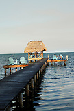 BELIZE, Caye Caulker, tourists relax on a pier by the water at sunset