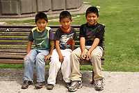 Three Mexican boys sitting on a park bench  in Cholula, Puebla, Mexico. Cholula is a UNESCO World Heritage Site.