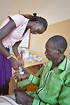 Elizabeth Nyanakak bandages the hand of a man in the clinic of the Loreto School in Rumbek, South Sudan. The school is run by the Institute for the Blessed Virgin Mary--the Loreto Sisters--of Ireland.