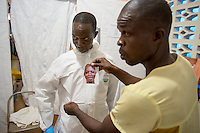 "Health care worker Kaifumba Komaro (left) dons his PPE, complete with his photo, as he prepares to enter the ""red zone"" to care for patients at the ELWA II Ebola Treatment Unit (ETU) in Monrovia, Liberia on Sunday, March 1, 2015. Occidental College professor Mary Beth Heffernan's PPE Portrait Project involves photographing health care workers and making disposable, adhesive prints of their images, which are then placed on the worker's PPE.<br /> (Photo by Marc Campos, Occidental College Photographer) Mary Beth Heffernan, professor of art and art history at Occidental College, works in Monrovia the capital of Liberia, Africa in 2015. Professor Heffernan was there to work on her PPE (personal protective equipment) Portrait Project, which helps health care workers and patients fighting the Ebola virus disease in West Africa.<br />