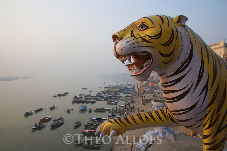 Tiger statue on high roof overlooking the Ghats (stairs) and Ganges River in Varanasi;  Varanasi has been a cultural and religious center in northern India for several thousand years, Varanasi, Uttar Pradesh, India