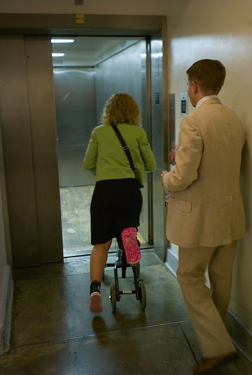 WASHINGTON, DC - July 30: Rep. Debbie Wasserman Schultz, D-Fla., rolls her way, scooter-style, onto an elevator on her way to the House chamber for a series of votes. She sprained her ankle and broke her leg Congressional Women's Softball Game July 15 sliding into second. With her is spokesman Jonathan Beeton. (Photo by Scott J. Ferrell/Congressional Quarterly)