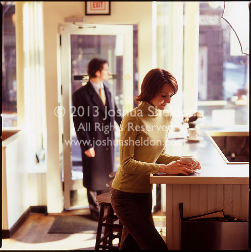 Woman in cafe with man in background