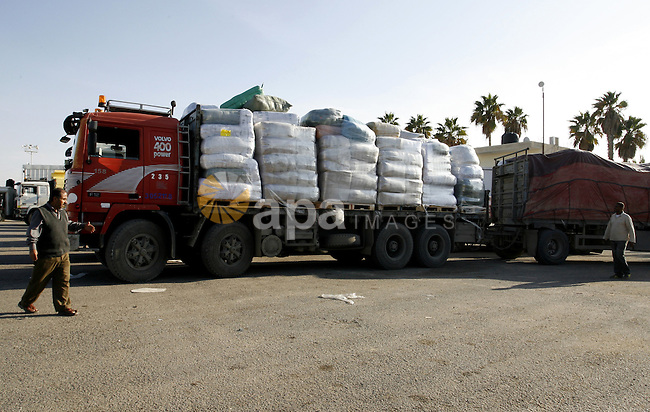 Palestinian workers walk past trucks loaded with supplies that entered the Gaza Strip from Israel through the Kerem Shalom crossing in Rafah in the southern Gaza Strip on November 5, 2014. UN peace envoy Robert Serry announced on November 4 that the temporary reconstruction mechanism for the war-torn Palestinian territory had begun operations, under the auspices of the newly formed Palestinian unity government, noting the urgency in providing cement and other materials to tens of thousands of damaged homes in Gaza ahead of winter. Photo by Abed Rahim Khatib