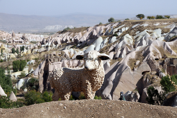 Small statue of a lamb accompanied by a real pigeon, with a Cappadocia, Turkey valley in the background
