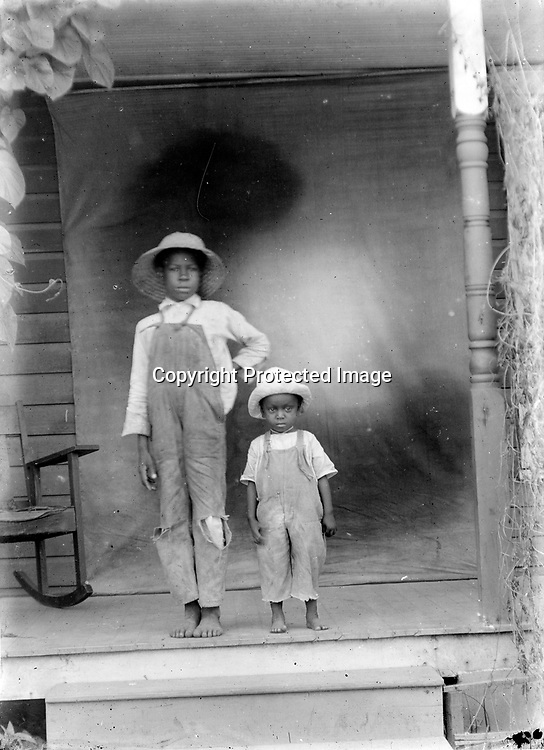 BOYS IN OVERALLS. While John Johnson took many photographs of children, seldom are they wearing clothing that looks ready for work or play. From their straw hats to bare feet, this pair looks ready to step off the porch and into summer.<br /> <br /> Photographs taken on black and white glass negatives by African American photographer(s) John Johnson and Earl McWilliams from 1910 to 1925 in Lincoln, Nebraska. Douglas Keister has 280 5x7 glass negatives taken by these photographers. Larger scans available on request.
