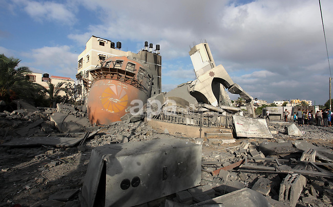 Palestinians gather around the remains of a mosque, which witnesses said was destroyed in an Israeli air strike before a 72-hour truce, in Khan Younis in the southern Gaza Strip August 11, 2014. Israeli negotiators were due in Cairo on Monday for talks on ending a month-old Gaza war with Palestinian militants, an Israeli government official said, after a new 72-hour truce brokered by Egypt appeared to be holding. Photo by Ramadan El-Agha