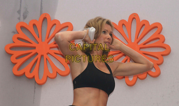 NELL McANDREW .Were amongst the celebrities launching Nintendo's new Wii game Wii Fit on the South Bank, London, England,.23rd April 2008..half length black crop top tummy midriff hands on head arms up.CAP/DS.©Dudley Smith/Capital Pictures