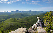 Zealand Notch - A hiker takes in the view of the Pemigewasset Wilderness from the summit of Zeacliff in the White Mountains of New Hampshire USA during the summer months. This view is just off the Appalachian Trail.