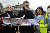 Actor Michael Sheen is presented with a painting by Mr Dennis Tippins of the mural of the Newport Chartist riots which took place in 1839. On the right is one of the rally organisers. <br />