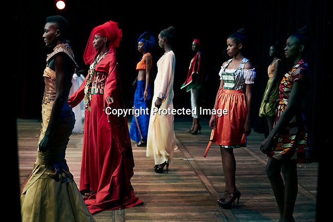 DAKAR, SENEGAL-JUNE 19: Models walk during a show at Dakar Fashion Week on June 19, 2014, at theatre Sorano in Dakar, Senegal. Seventeen Senegalese, African and foreign-based designers showed their collections during the 12th edition of Dakar Fashion week. The evening's event showcased a fashion film produced by designer Adama Paris and installation fashion show. (Photo by Per-Anders Pettersson)
