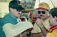 Davey Allison, with his arm in a sling talks with Ernie Irvan, center, and Tony Glover, R, Winston 500, Talladega Superspeedway, Talladega, Alabama, May 1992.(Photo by Brian Cleary/bcpix.com)