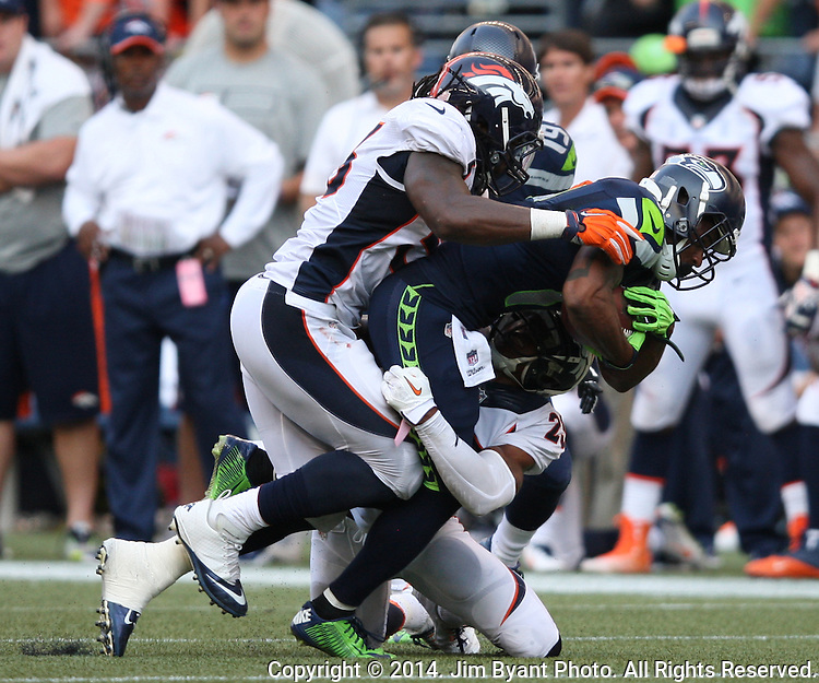 Seattle Seahawks  wide receiver Percy Harvin (11) is tackled by Denver Broncos linebacker Nate Irving (56) and safety Rahim Moore (26) after picking 11 yards in overtime at CenturyLink Field in Seattle, Washington on September 21, 2014. The Seahawks won 26-20 in overtime.     ©2014. Jim Bryant Photo. All rights Reserved.