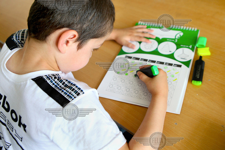 Seven year old Ruslan (the name is changed) colouring a chart while he attends Health Centre No. 10 where he is being treated for nosocomical HIV infection.