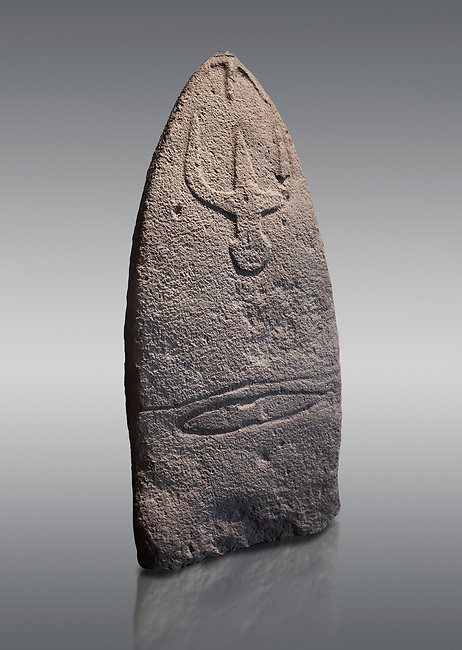 Late European Neolithic prehistoric Menhir standing stone with carvings on its face side. The representation of a stylalised male figure starts at the top with a long nose from which 2 eyebrows arch around the top of the stone. below this is a carving of a falling figure with head at the bottom and 2 curved arms encircling a body above. at the bottom is a carving of a dagger running horizontally across the menhir. Excavated from Genna Arrele II. Menhir Museum, Museo della Statuaria Prehistorica in Sardegna, Museum of Prehoistoric Sardinian Statues, Palazzo Aymerich, Laconi, Sardinia, Italy. Grey background.