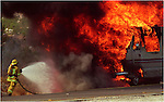 10/2/93 Desert Sun photo by Rodrigo Pena.  Palm Springs firefighter Paul Duenas battles a blazing motor home on Highway 111 near the Whitewater Bridge.