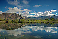 The clear water of an alpine lake in Tibet reflects the beautiful landscape just outside of Lhasa.