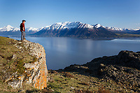 Spring landscape of male/man hiker taking photo with smart /cell phone of Chugach Mountains in Chugach State Park high above Seward Highway and Turnagain Arm.  Kenai Mountains backgound  <br /> <br /> (C) Jeff Schultz/SchultzPhoto.com