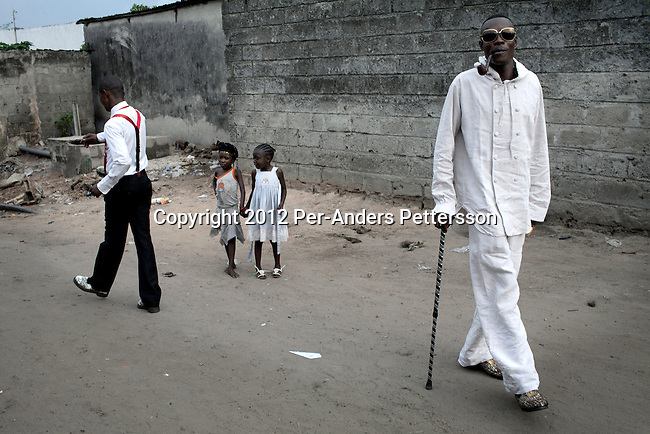 """KINSHASA, DEMOCRATIC REPUBLIC OF CONGO - FEBRUARY 12: Jika (r), a senior Sapeur with a friend close to his home in the Mombele area on February 12, 2012 in Kinshasa, DRC. Jika loves Japanese fashion especially the designer Yohji Yamamoto. The word Sapeur comes from SAPE, a French acronym for Société des Ambianceurs et Persons Élégants or Society of Revellers and Elegant People and it also means, to dress with elegance and style"""". Most of the young Sapeurs are unemployed, poor and live in harsh conditions in Kinshasa,  a city of about 10 million people. For many of them being a Sapeur means they can escape their daily struggles and dress like fashionable Europeans. Many hustle to build up their expensive collections. Most Sapeurs could never afford to visit Paris, and usually relatives send or bring clothes back to Kinshasa. (Photo by Per-Anders Pettersson)"""