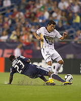 New England Revolution midfielder Joseph Niouky (23) slide tackles Pumas UNAM forward Juan Carlos Cacho (11). The New England Revolution defeated Pumas UNAM in SuperLiga group play, 1-0, at Gillette Stadium on July 14, 2010.